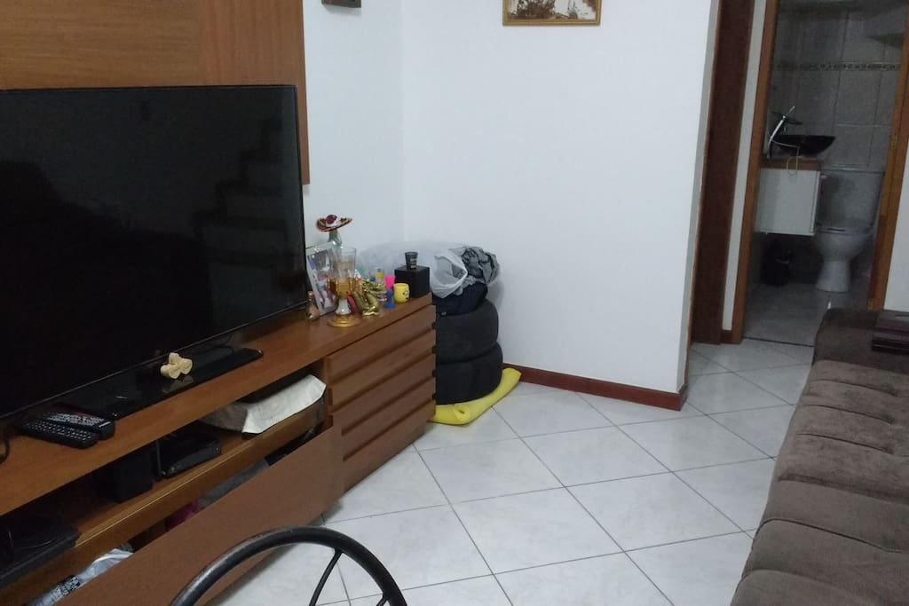 sala com tv e sofa retratil