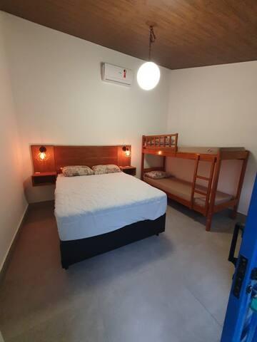 Quarto 2, com banheiro, cama de casal e um beliche