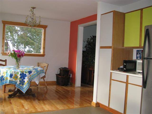 Bright kitchen and dining room with view unto the backyard.
