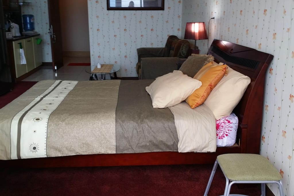 Comfortable Queen  size bed with summer quilt and sofa area