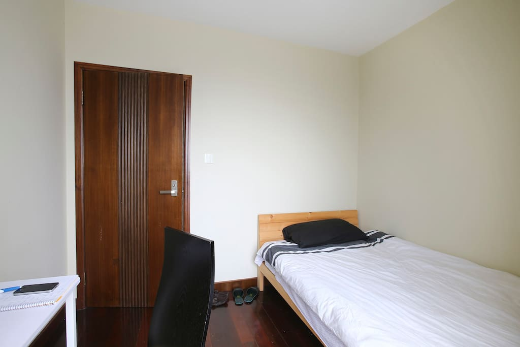 private room with double bed, desk, chair, and wardrobe