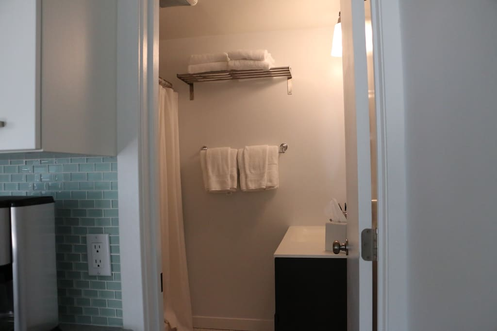 A full bath with white linens.