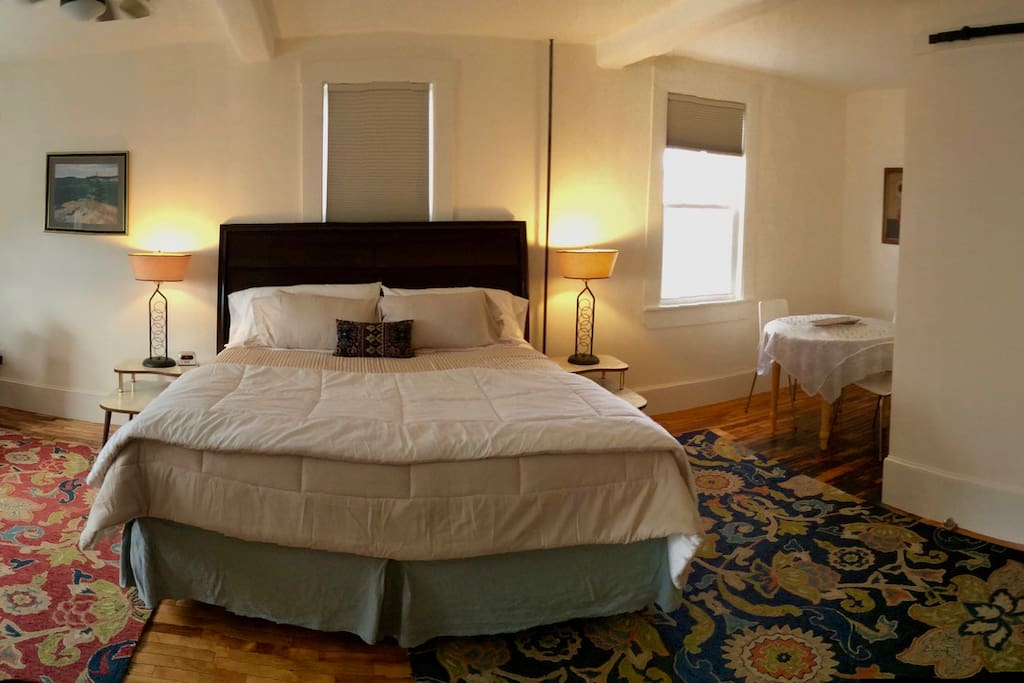 View of bed with dining nook on right.