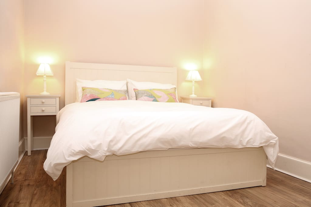 King size bed with bedside tables, wardrobe and dressing table.