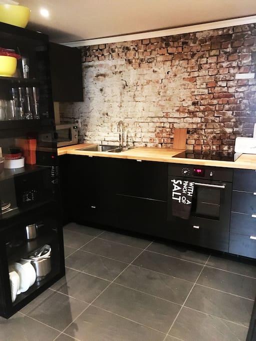 Ny kjellerleilighet i moderne stil, her svart kjøkken med integrerte kvitevarer