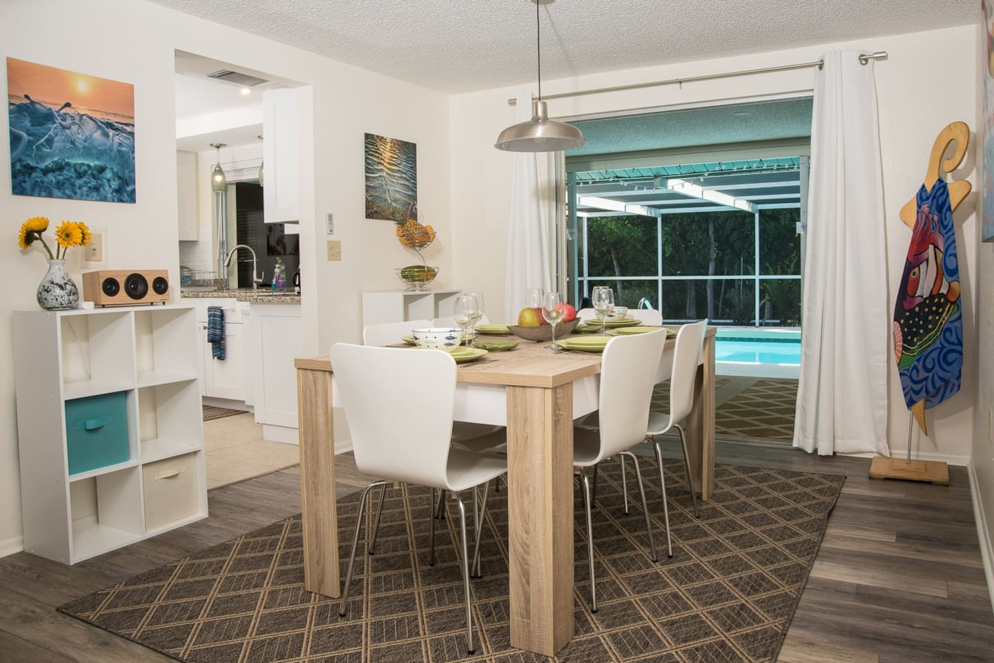 Open floor plan with living room & dining area with sliding glass doors opening to the pool area