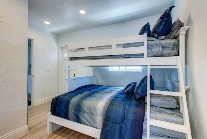 Bedroom with large full size bed with twin size bed above.