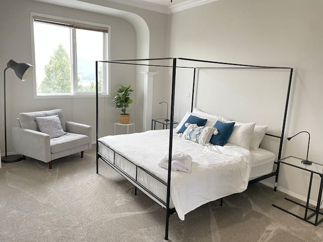 Luxurious king bed in the upstairs master suite with attached 4pc en-suite. Read a book in the oversized sofa chair.