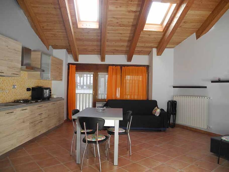 Cucina con balcone esterno, lavastoviglie, tv, camino a legna, forno elettrico.