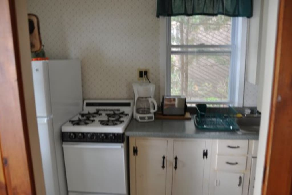 Kitchen with refrigerator, stove, coffee maker and toaster.