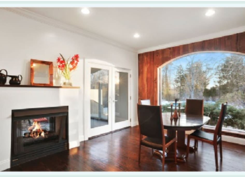 The dining room features a Double sided fireplace and walnut wide plank floors.