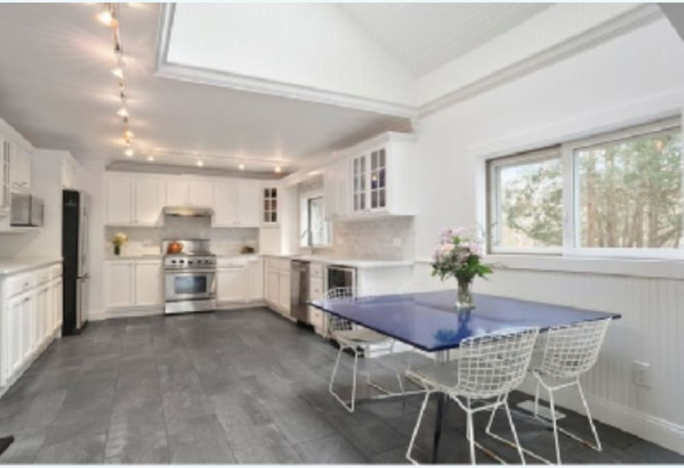 The spacious kitchen featuring white marble countertops and italian marble flooring.