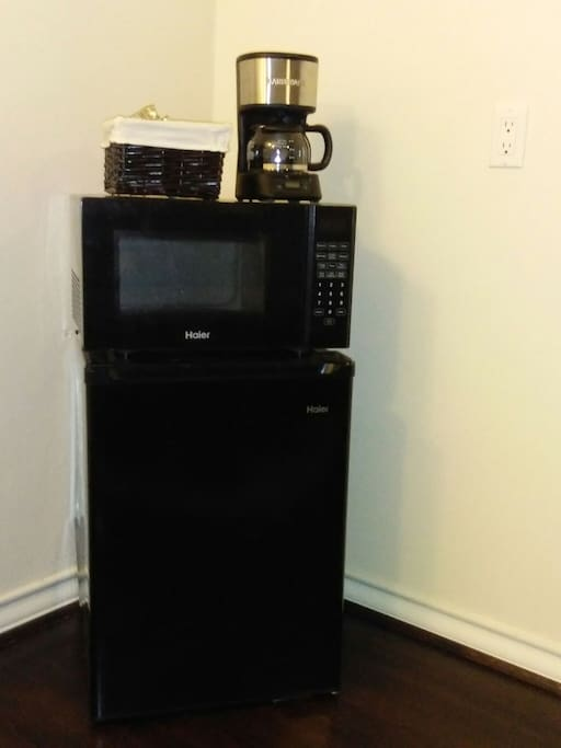 Microwave, mini-fridge, coffee maker, and coffee and tea selection provided.