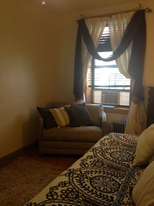 Room has oversized sofa, A/C and ceiling fan