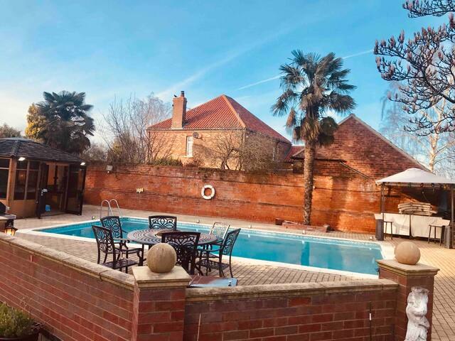 Hot tub building, swimming pool, bbq area and bar.
