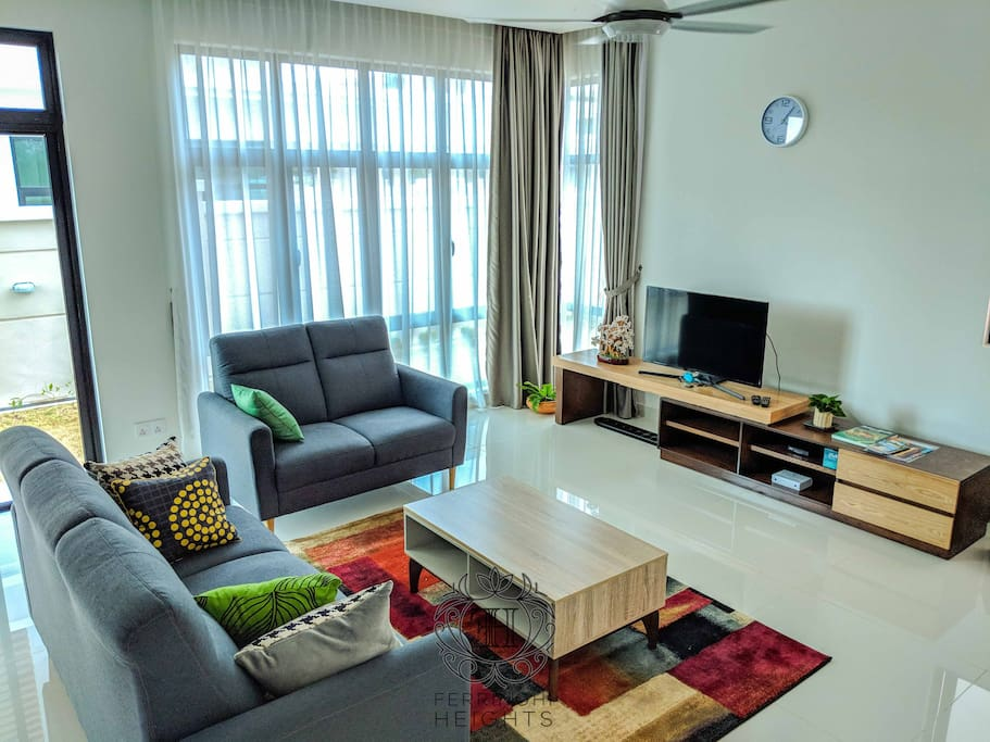 "Ground floor: Large living room with elegant sofa, coffee table, 40"" LED TV and ceiling mounted air-conditioner"