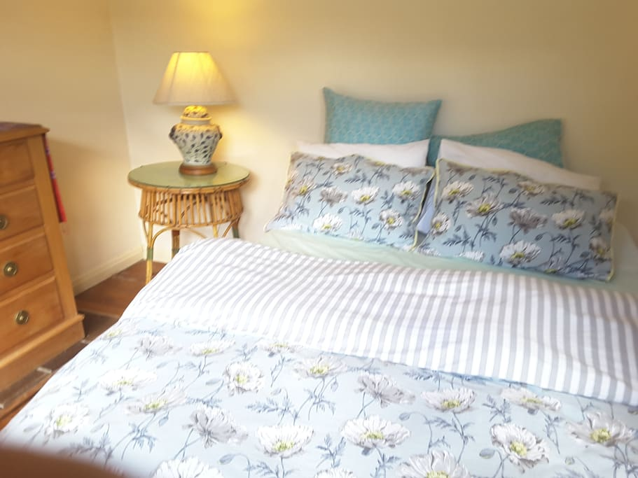 The comfortable first bedroom with a view of the garden