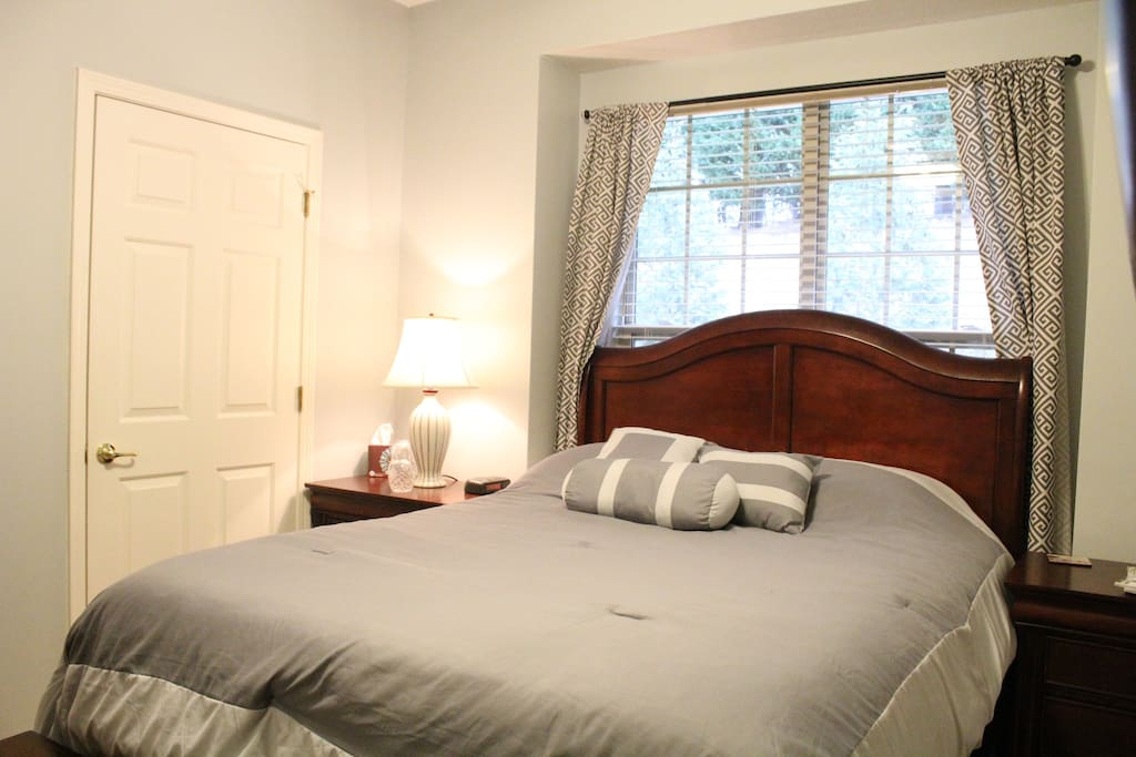 Queen sized bed in guest room with adjacent private bathroom.