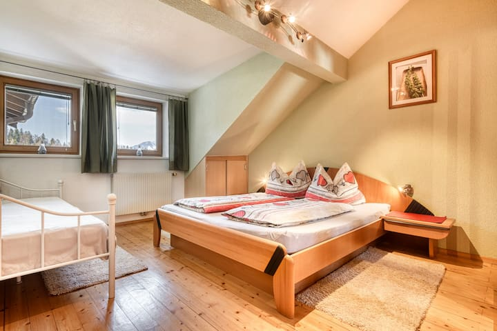 Schlafzimmer mit Doppelbett und einem Einzelbett