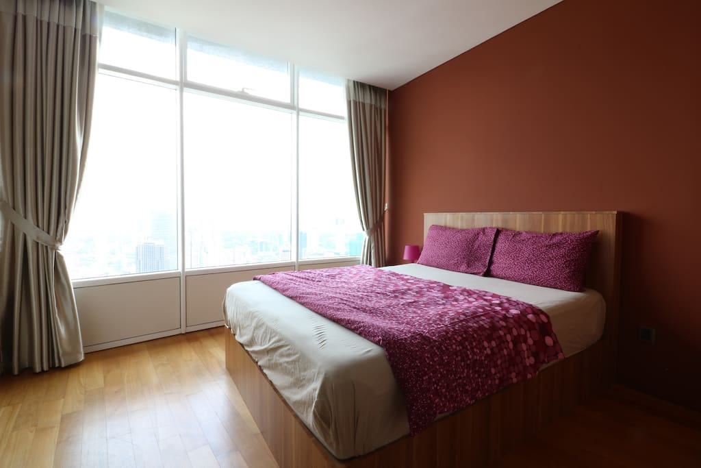 Common bedroom with a Queen size bed soothing yellow light and air cond along with a breath taking city view