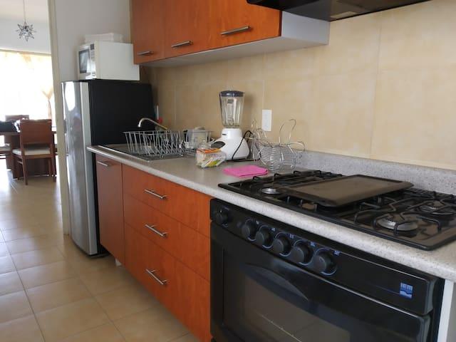 Cocina equipada  con diversos utensilios, vajilla y batería de cocina.