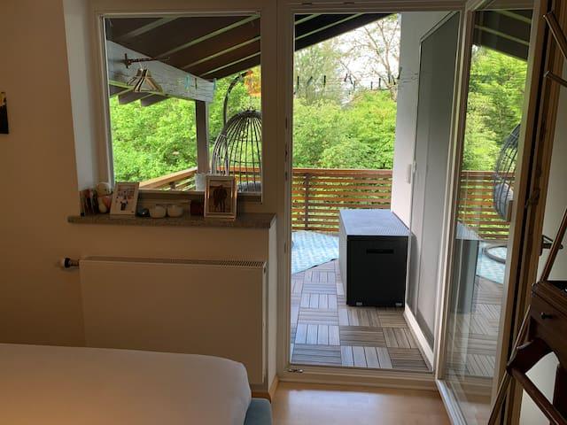Schlafzimmer 1 mit Zugang zum überdachten Balkon und Blick ins Grüne
