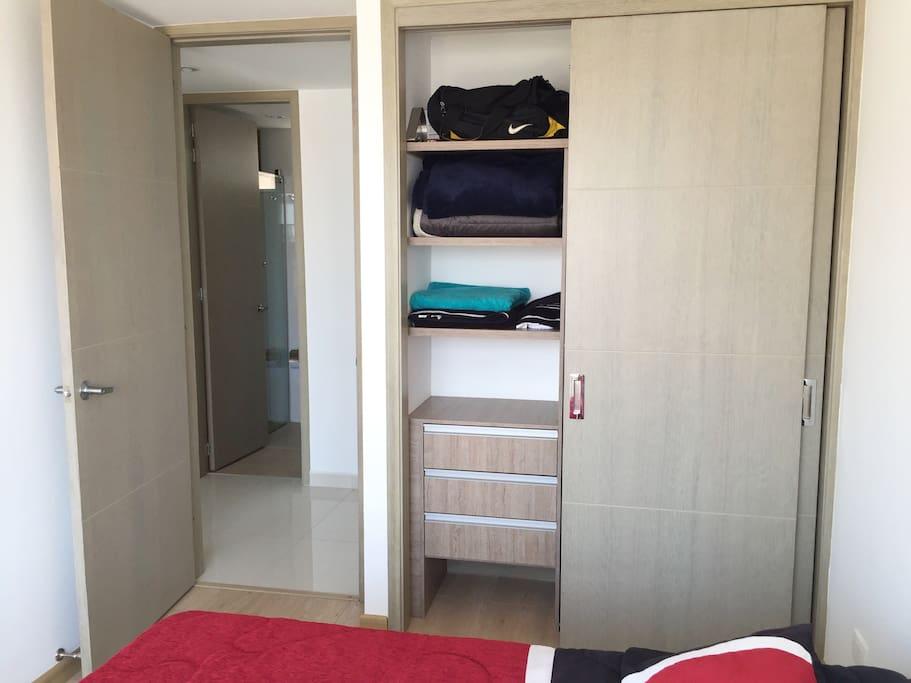 Amplio closet, incluye juego de sabanas, cubrecama, almohadas y perchas de ropa.
