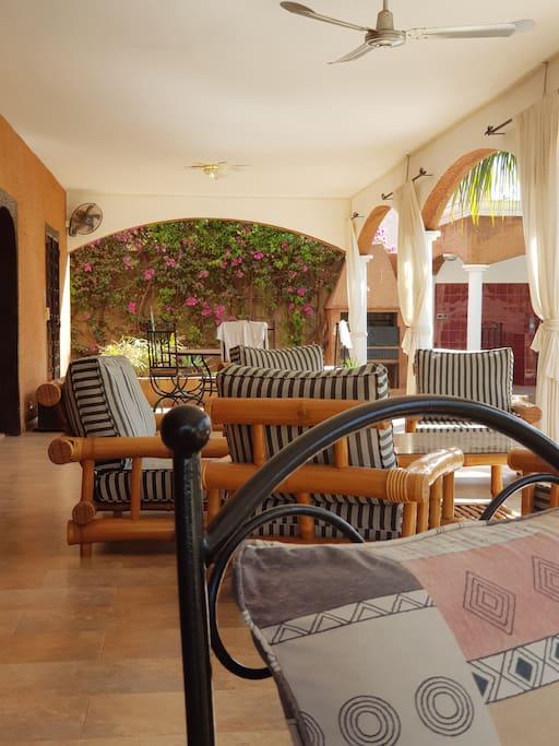 Vue sur les salons en fer forgé, en bois et sur la salle à manger judicieusement disposés sur la terrasse