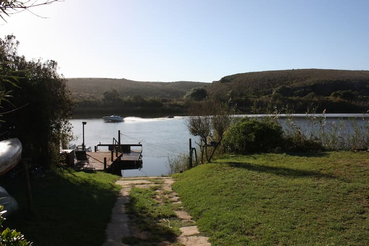 View down the slipway across the floating jetty with skiboat in the background. The Breede River is well known for its excellent skiing conditions