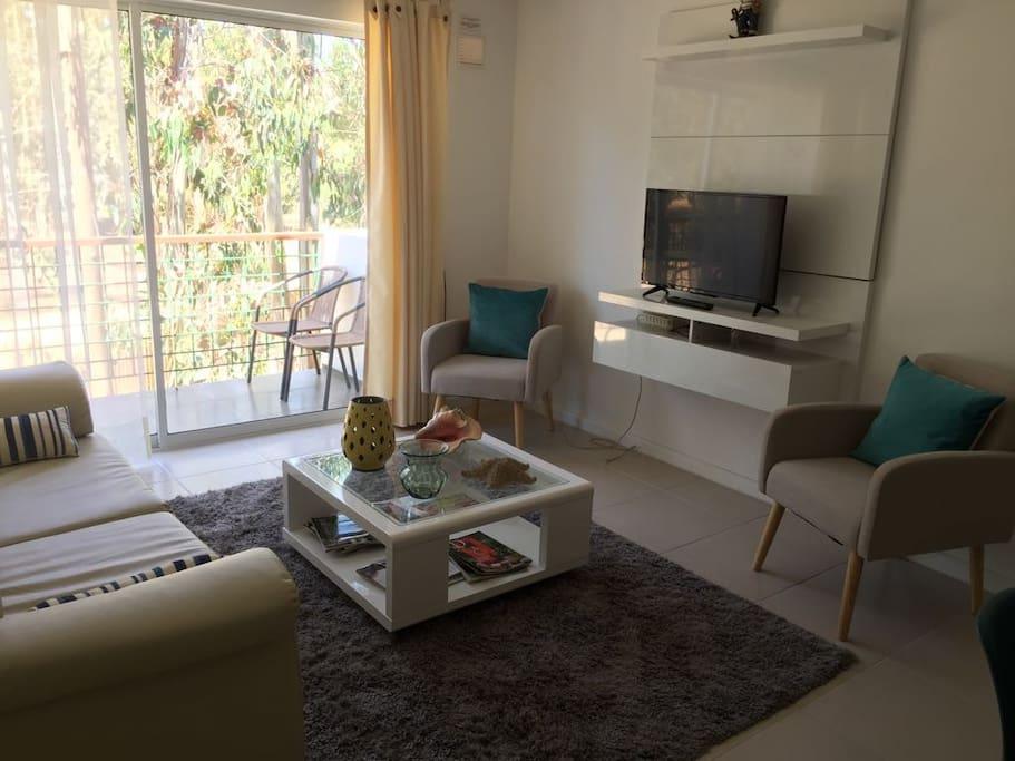 Cómodo living con televisión por cable y un hermoso balcón