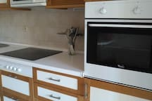 The kitchen with oven,microwave and electric cooker.