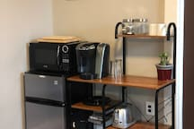 The kitchenette includes an apartment fridge, microwave, Keurig Coffeemaker, toaster, plates, glasses, utensils, and towels. The kitchenette is supplied with complimentary beverages, water, coffee pods, cream, & sugar.
