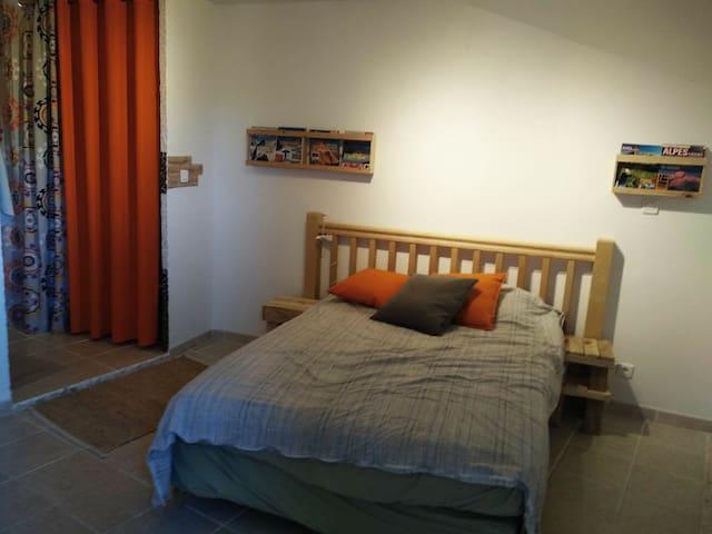 """""""En bas"""" de la maison : la chambre 2 places avec possibilité de rajouter un lit parapluie. Accès sur la salle de bain privée sur la gauche"""