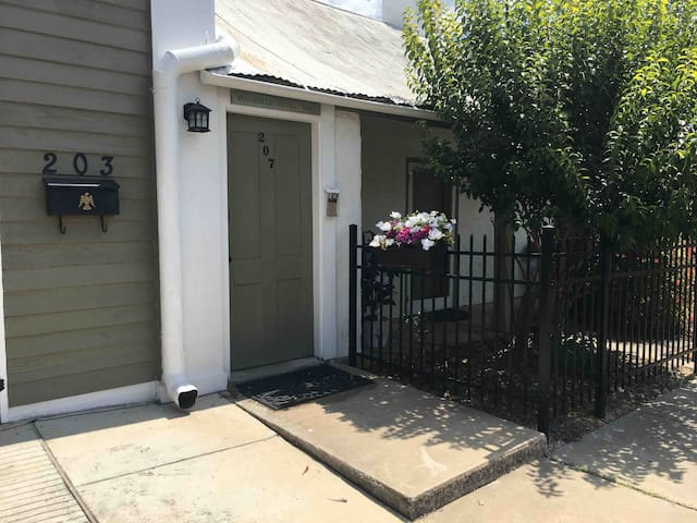 This is the entrance to the suite. The door is painted green. This is on the side of S Crockett St. Behind the iron fence is the original 1847 Magnolia Hotel and now our residence.