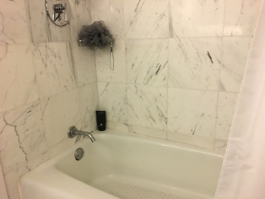New bathtub with marble tiles.