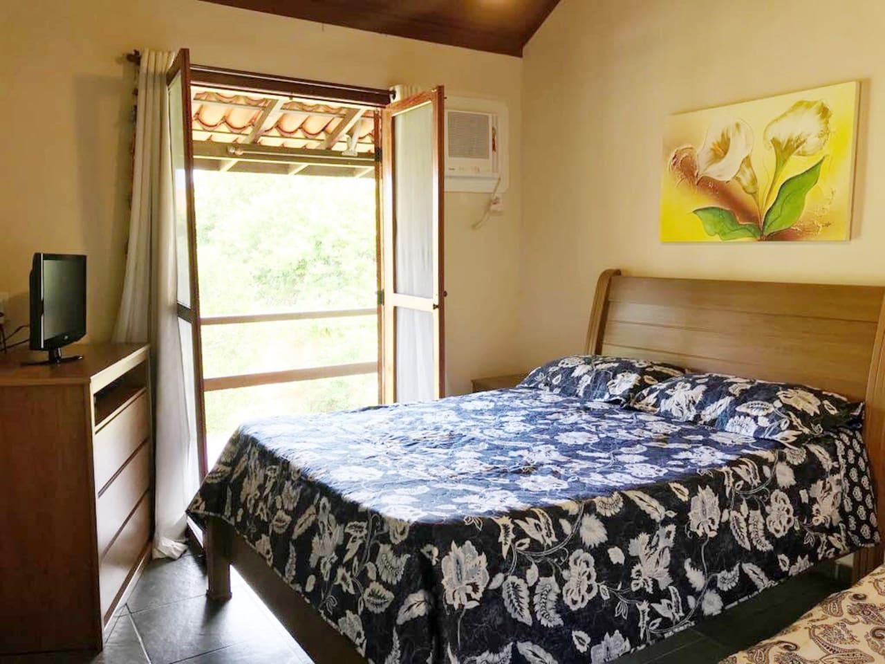 Quarto com cama de casal, cama auxiliar de solteiro, ar condicionado, banheiro e cortina com blackout