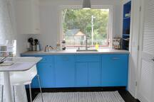 Gourmet kitchenette features toaster/oven, 2-burner cooktop, dishwasher, refrigerator w/freezer.