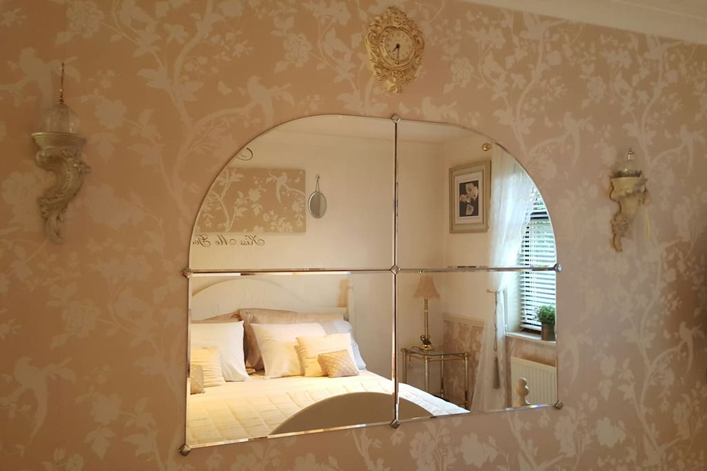Large beveled edge mirror opposite king size bed.