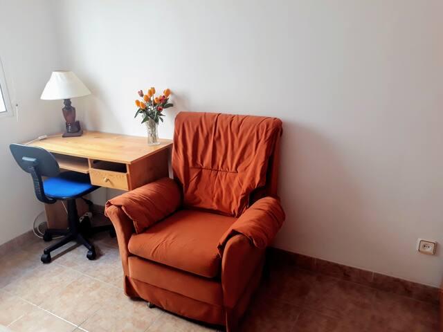 Habitación privada con escritorio y sofá