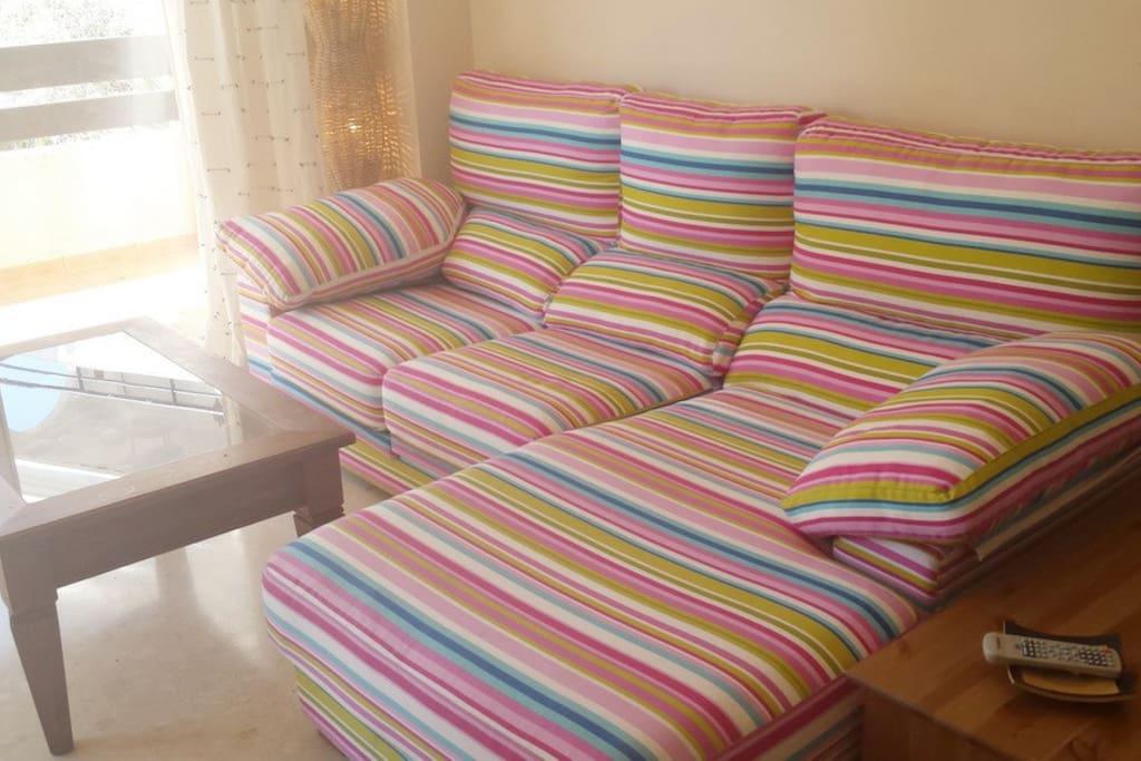Un sofá chaise long muy alegre super cómodo en el que descansar..