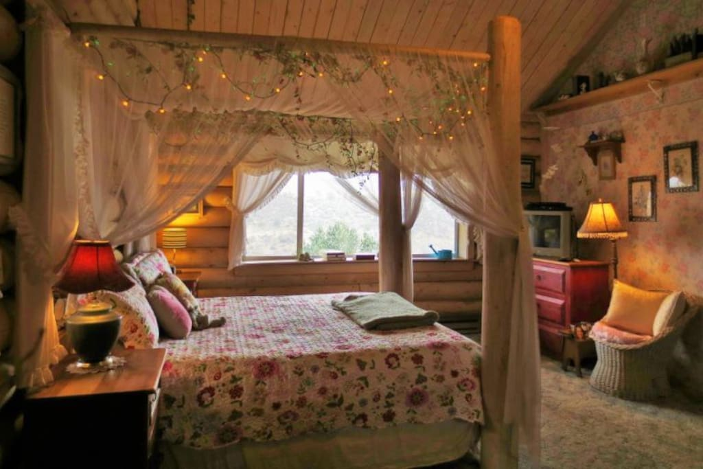 King Bed with Log Post Canopy Decorated with Lights and Flowers