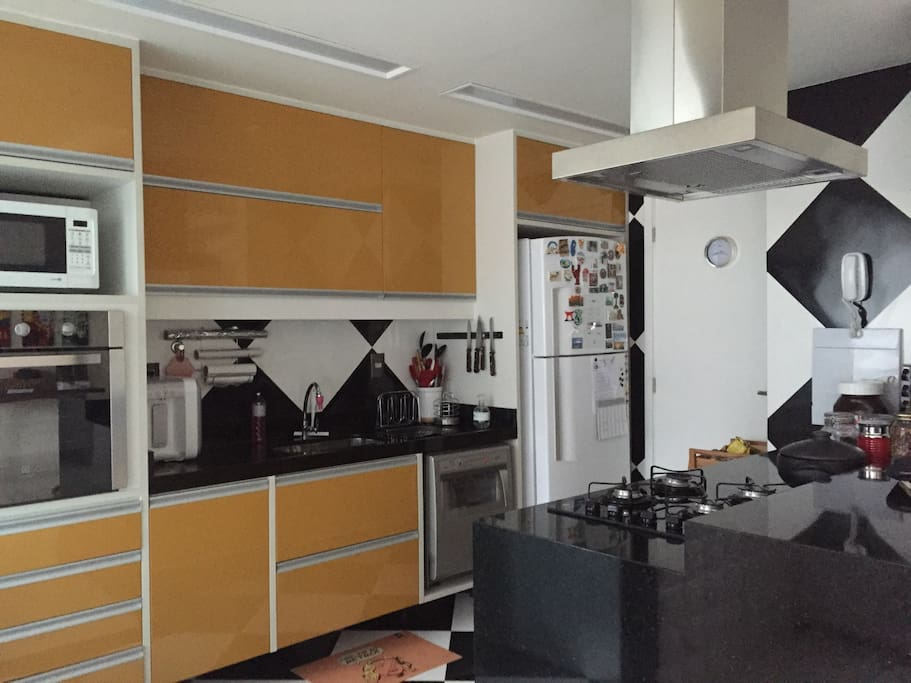 This is a close-up picture of the kitchen. There is a cook-top, a freezer, a microwave, an oven and a cleaning machine.