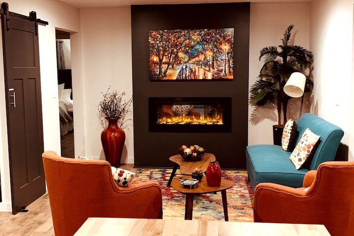 Sitting room off of kitchen island with orange swivel chairs to that can enjoy the fire or turn to talk to the chef while cooking.