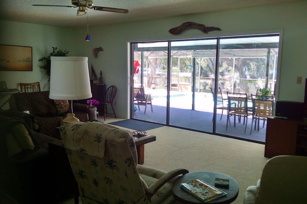 Comfy living room looking out at the pool and canal