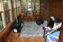 Game room with Xbox and arcade and table overlooking creek