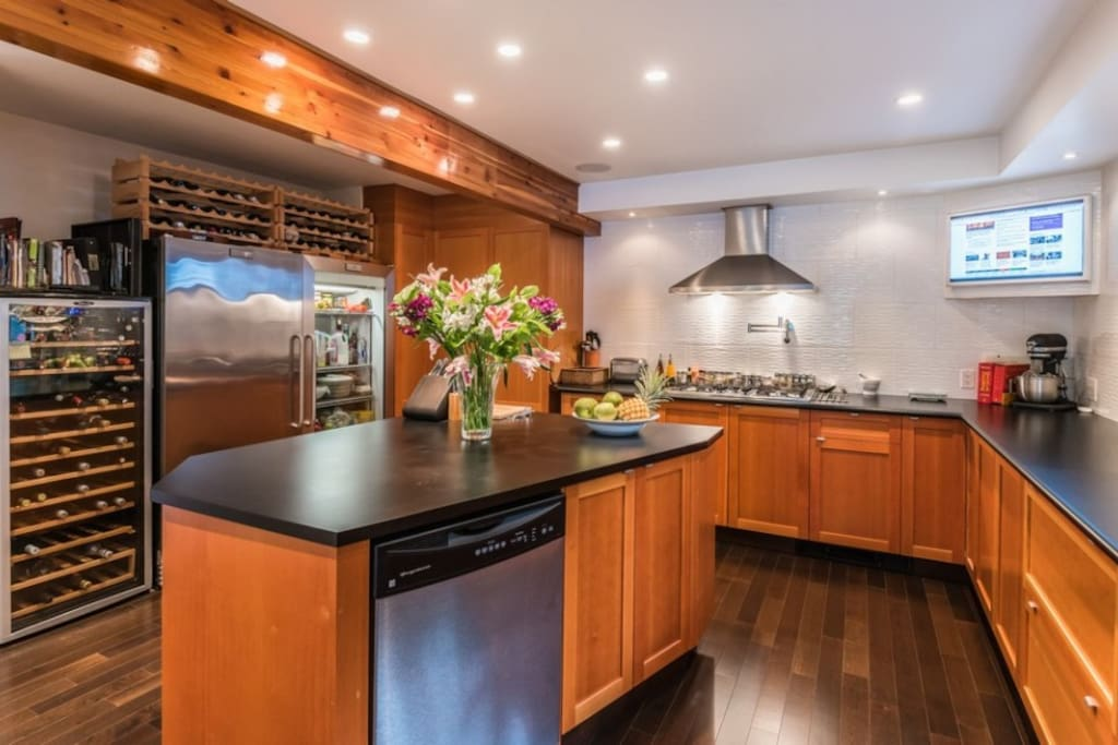 Open Chef's Kitchen w/ gas range, oven, commercial fridge & freezer, drinks cooler, double sink, utility island and dishwasher. Great for communal food preparation.