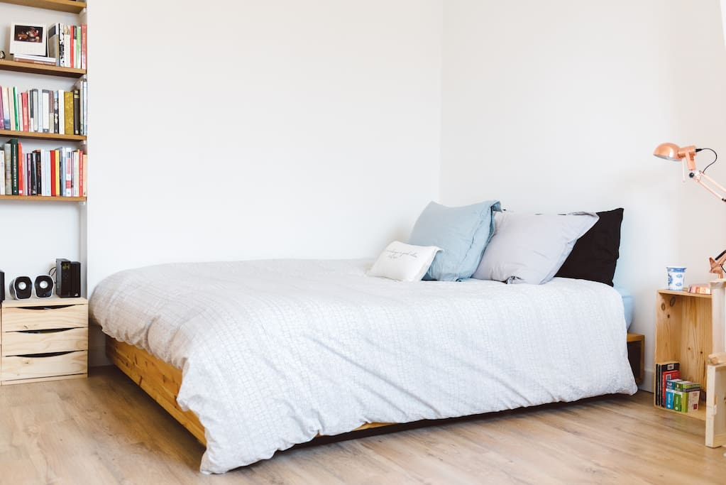 Queen size bed with goosefeather pillows and a down comforter.