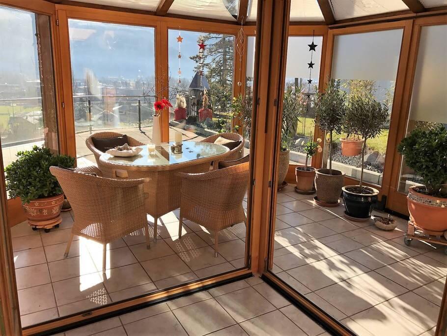 Sonniger Wintergarten verbindet das offene Wohnzimmer mit der grossen Terasse   The sunny winter garden connects the open living room with the big terrace