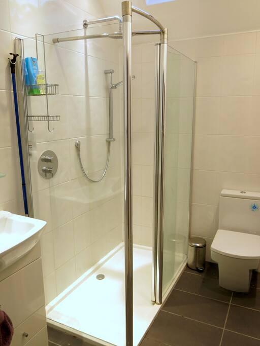The bathroom has a heated floor and a spacious shower with a rain-storm head.