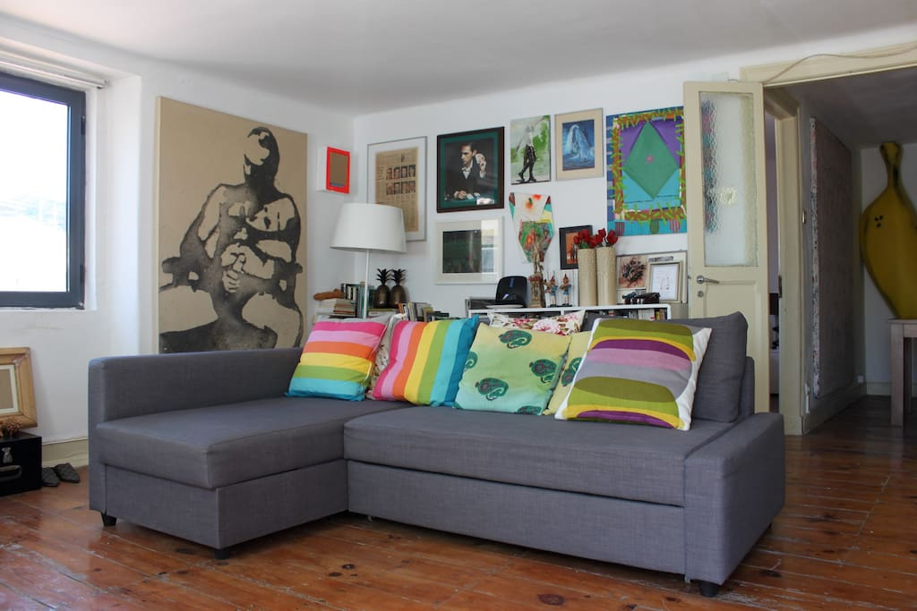living room with part of our art collection and a couch easily transformed into an extra double bed